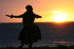 夕日を背景にフラダンスを踊る女性